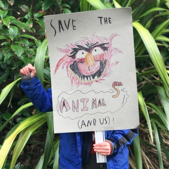 A child holds up a homemade placard with the message 'save the animals (and us)