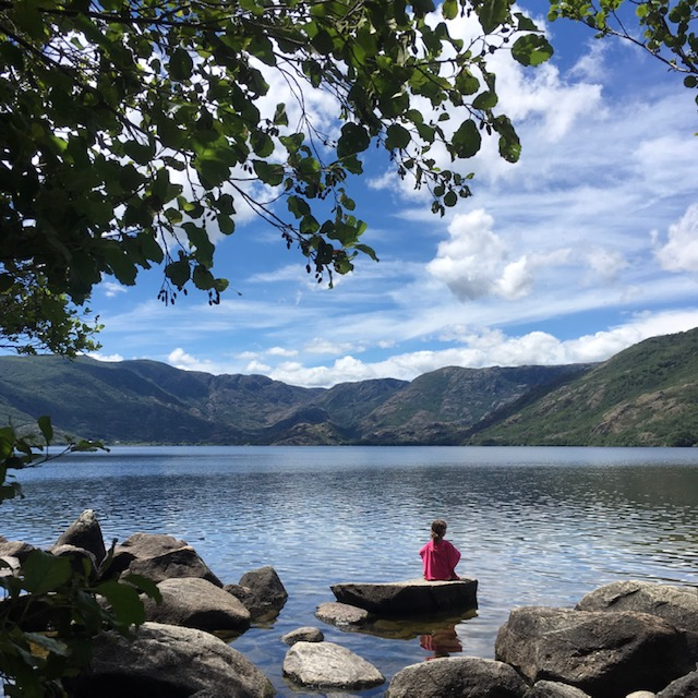 girl sits on a rock looking out at a lake