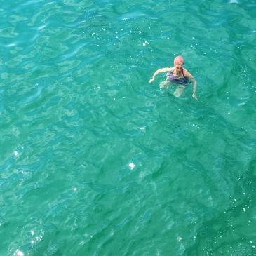 A beautiful older woman swims joyfully in a turquoise sea