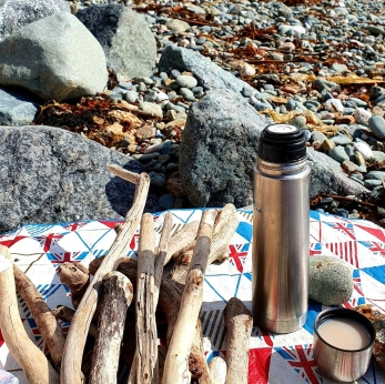beach picnic rug with flask and driftwood