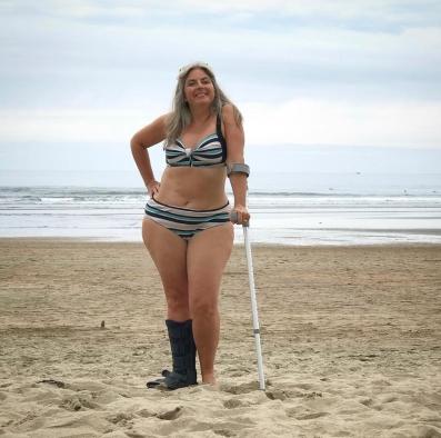 Woman balancing on crutch on beach in bikini
