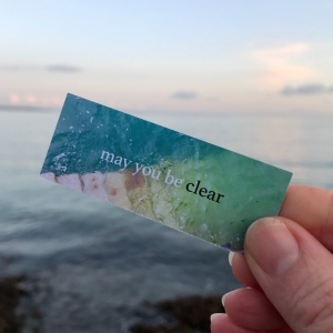 May you be clear - A Sea Soul Blessing card held up by a hand in front of the sea
