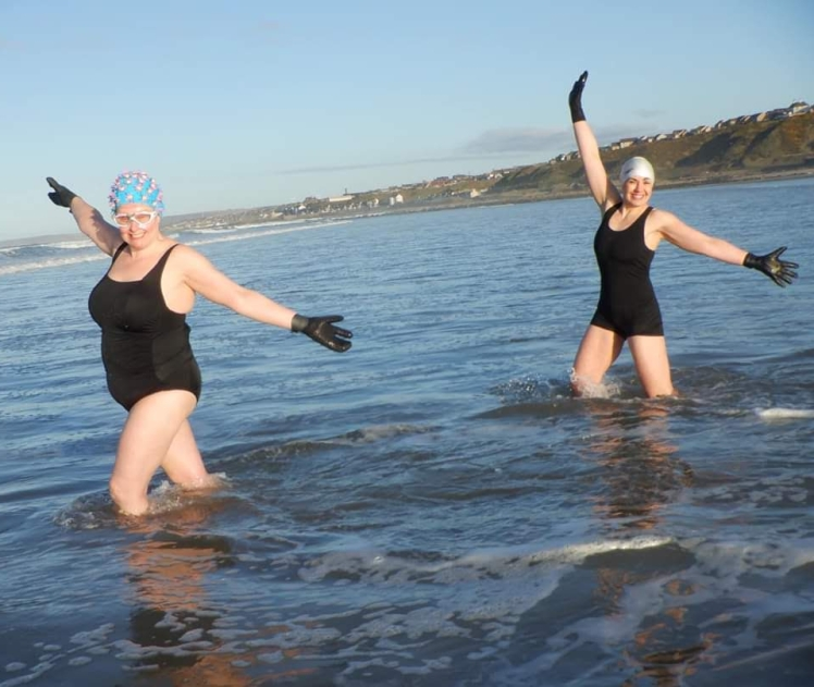 Two sea swimmers celebrating the blessings of the sea, connecting to nature: Lynda uses the sea and Sea Soul Blessings to explore her faith.